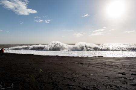 Grosse, unberechenbare Wellen am schwarzen Strand