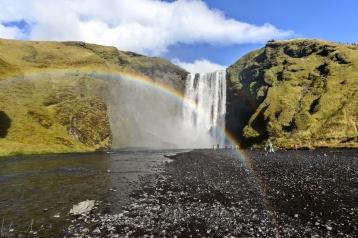 Die Gischt des Wasserfalls erzeugt in der Sonne einen Regebogen
