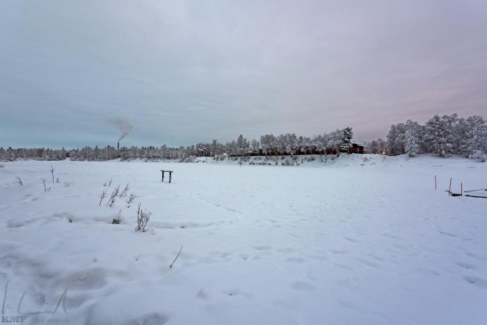 Das Hotel Ivalo von gegenüberliegenden Ufer des zugefrohrenen Fluss Ivalojoki